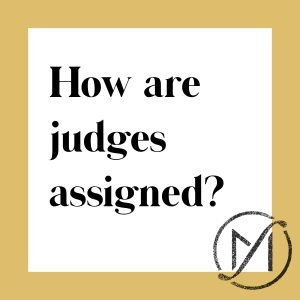 white square with a gold border and the black words how are judges assigned and the Freed Marcroft logo in the lower right corner
